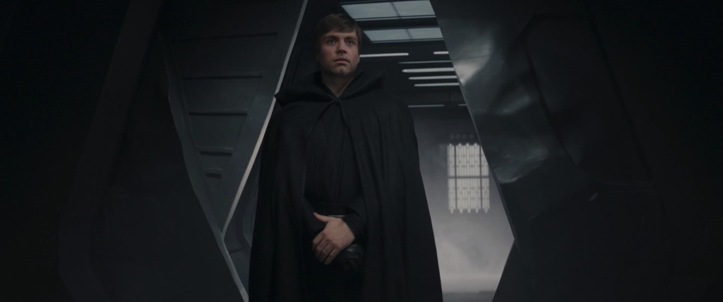 Luke Skywalker stands at the door, looking for the child.
